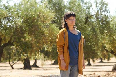 Alma (Anna Castillo) steht im Olivenbaum-Hain ihrer Familie. - Foto: Real Fiction